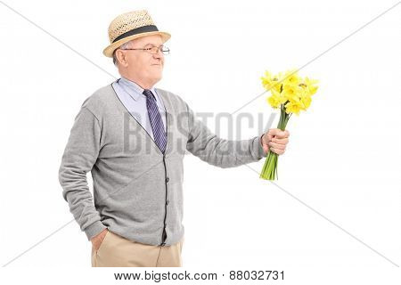 Cheerful senior gentleman holding a bunch of yellow tulips isolated on white background
