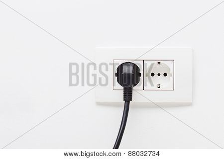 Black electric chord plugged into a white electricity socket on white background