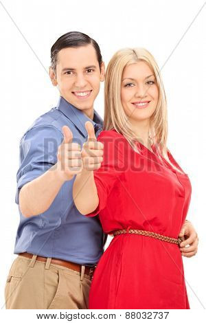 Vertical shot of a young couple posing sideways and giving thumbs up isolated on white background