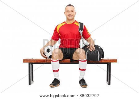 Studio shot of a young guy in football uniform holding a football and carrying a sports bag seated on a wooden bench