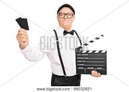 Studio shot of an older movie director holding a clapperboard and two tickets isolated on white background