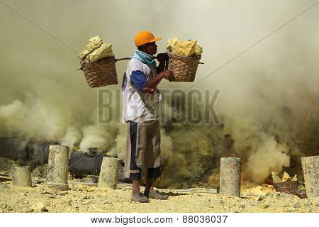 KAWAH IJEN, INDONESIA - AUGUST 8, 2011: Miner carries baskets with sulphur in fumes of toxic volcanic gas at the sulphur mines in the crater of the active volcano of Kawah Ijen, East Java, Indonesia.