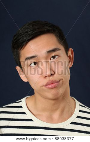 Funny young Asian man making face