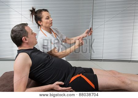 Female Doctor Examining X-ray Of A Sportman Patient