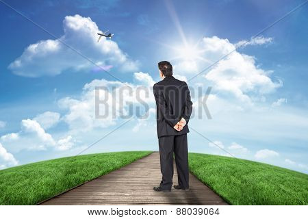 Mature businessman looking and considering against road leading out to the horizon