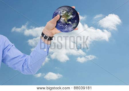 Businessman holding hand out in presentation against cloudy sky