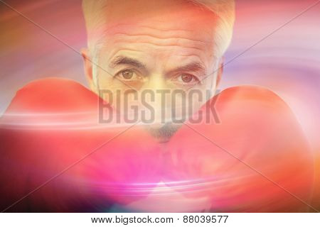 Close-up portrait of a determined senior boxer against sunrise sky