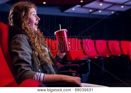 Young woman watching a film at the cinema