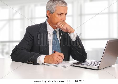 Mature businessman seated at his desk in a modern office building. In front of him is a laptop and note pad. The man is deep in thought.