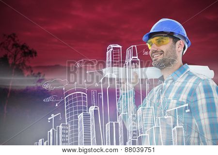 Smiling architect looking away while holding blueprint against trees and mountain range against cloudy sky