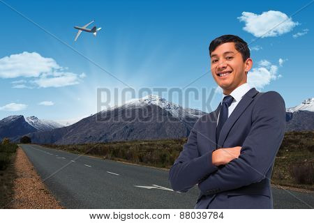 Smiling asian businessman with arms crossed against road leading out to the horizon