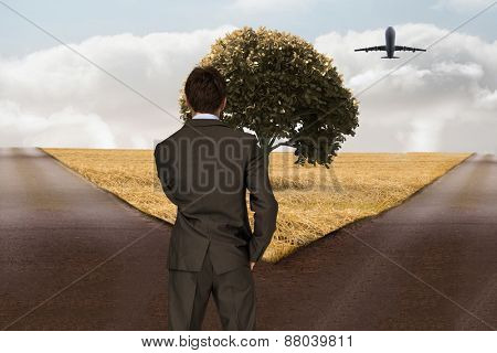 Thinking businessman against crossroads