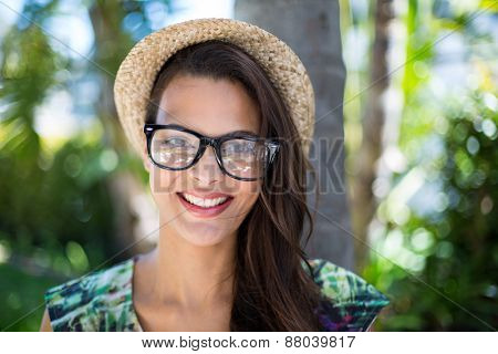 Smiling beautiful brunette looking at camera with palm tree behind her