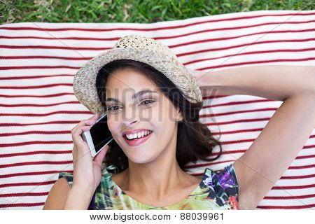 Smiling beautiful brunette lying on the blanket and speaking on the phone