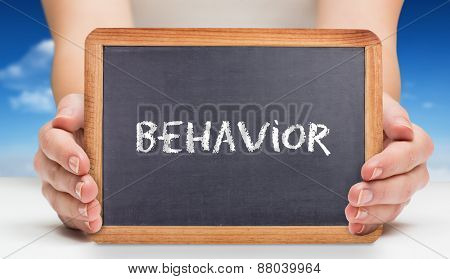 The word behavior and females hands showing black board against bright blue sky with clouds