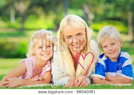 Mother with her children lying down during the summer against valentines love hearts