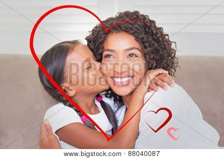 Hearts against pretty mother sitting on the couch with her daughter kissing her cheek