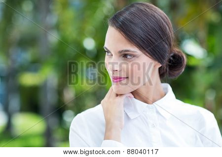 Thoughtful woman with hand on chin outside