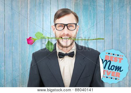 Geeky hipster holding rose between teeth against wooden planks