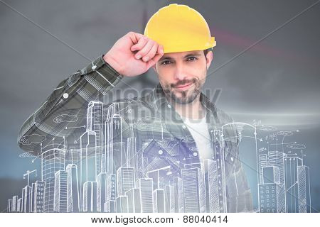 Smiling Handyman holding helmet against windmill spinning over a green field