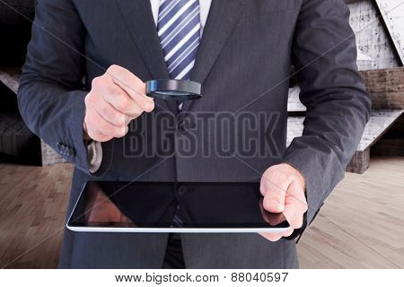 Businessman looking at tablet with magnifying glass against abstract room
