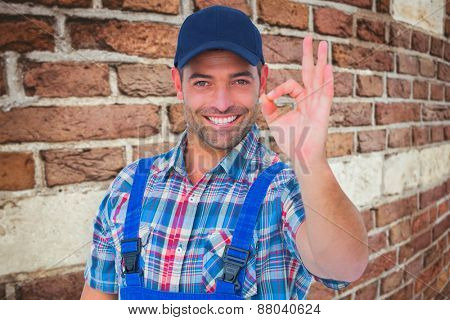 Portrait of smiling repairman gesturing okay against red brick wall