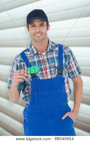 Confident plumber showing green card against grey shutters