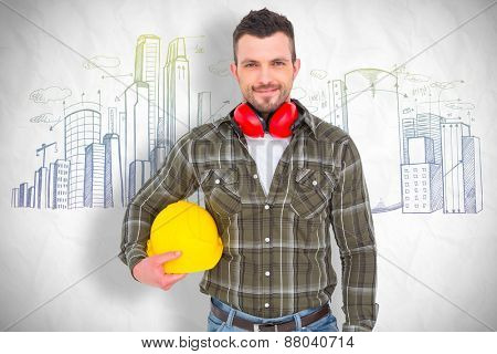 Handyman with earmuffs holding helmet against crumpled white page