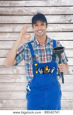 Plumber holding plunger while gesturing OK sign against digitally generated grey wooden planks