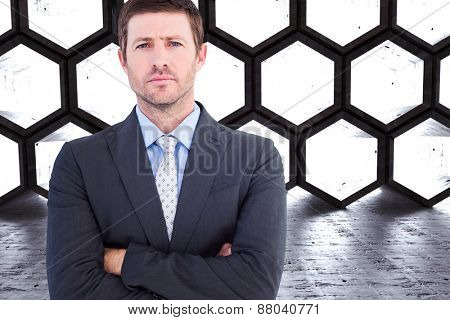Businessman looking at the camera against hexagon room