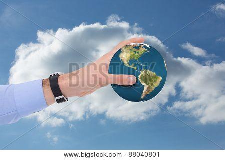 Businessman showing with his hand against cloudy sky