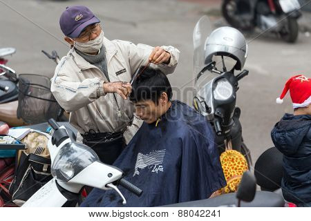 HANOI, VIETNAM, DECEMBER 15, 2014: A nomad hairdresser is working outside in the city , his customer is sitting on his motorbike in Hanoi, Vietnam.