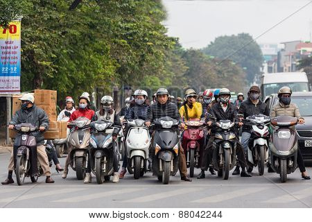 HANOI, VIETNAM, DECEMBER 15, 2014: Front wall of People waiting at the traffic light on their motorbike in Hanoi, Vietnam