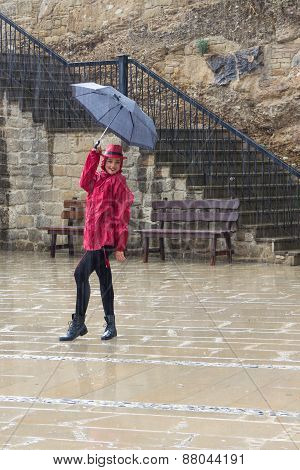 Young Happy Woman With An Umbrella Dancing In The Rain.
