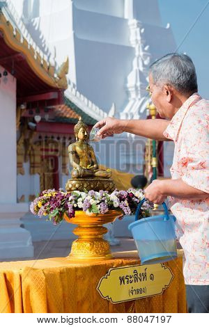 An older man with him descendant are pouring water onto Buddha image