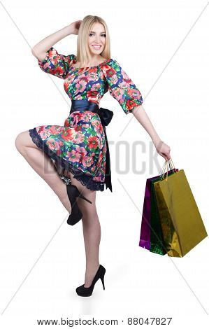 Portrait of happy female shopaholic with several paper bags
