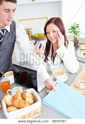 Couple Of Businesspeople Having Breakfast In The Kitchen