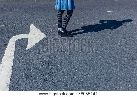 Woman Standing Outside By Big Arrow