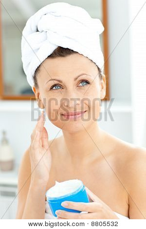 Positive Young Woman With A Towel Putting Cream On Her Face In The Bathroom