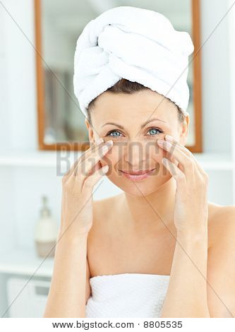 Cute Young Woman With A Towel Putting Cream On Her Face In The Bathroom