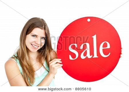"""Bright Young Woman Holding A Red Panel Where """"sale"""" Is Written"""