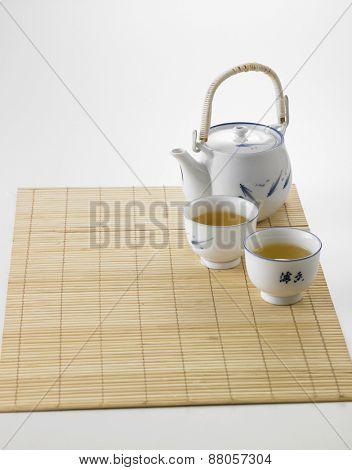 Japanese white tea pot on the bamboo mat