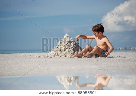 Cute little son building sand castle at beach