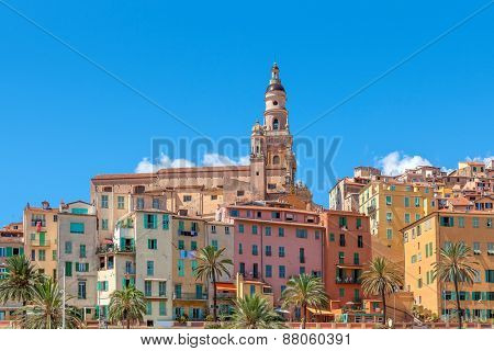 Belfry among colorful houses under blue sky in Menton - small town on French Riviera.