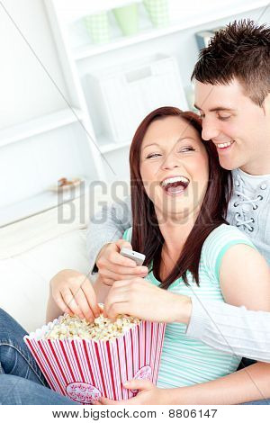 Laughing Young Couple Lying On The Sofa With Popcorn And Remote