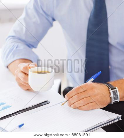 business and education concept - businessman drinking black coffee in office