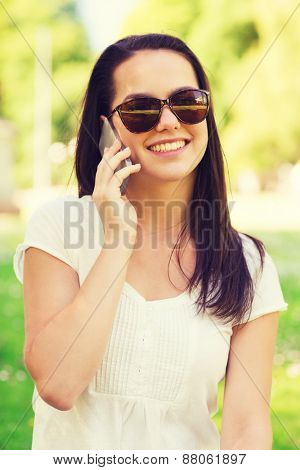 lifestyle, summer, vacation, technology and people concept - smiling young girl with smartphone calling in park