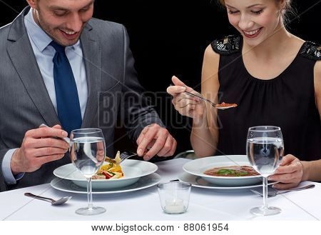 restaurant, food, people, date and holiday concept - close up of happy couple eating at restaurant