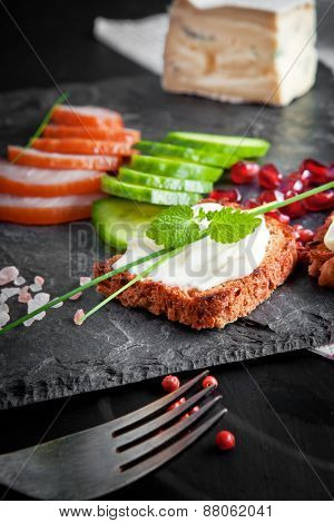 Cheese sandwich with vegetables and ham on a slate plate