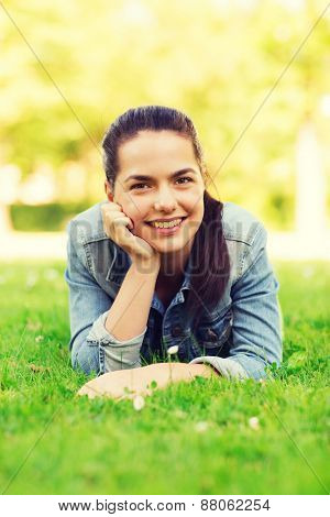 lifestyle, summer vacation, leisure and people concept - smiling young girl lying on grass in park